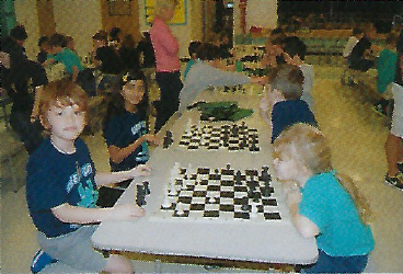 Young boy and girl playing and learning chess together.